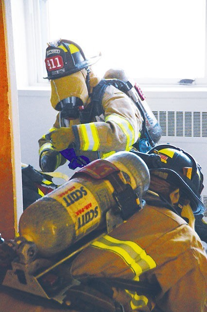 "During search-and-rescue training at Ft Belvoir Building 808, Dec. 15, fire crews from Fairfax County Engine 411 cover their masks with hoods for a ""black out"" drill, which simulates heavy black smoke in a room. Since the firefighters cannot see, they must search a room by listening and feeling."